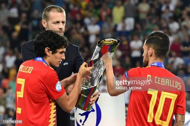 President Aleksander Ceferin hands the winners' trophy to Spain's midfielder Dani Ceballos and Spain's defender Jesus Vallejo after Spain won the...
