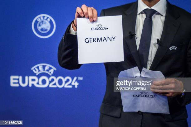 TOPSHOT UEFA president Aleksander Ceferin shows the name of Germany elected to host the Euro 2024 fooball tournament during a ceremony on September...