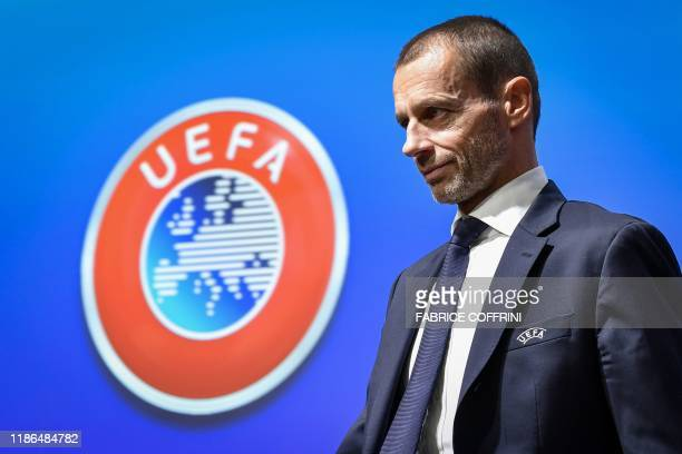 President Aleksander Ceferin walks past a sign with the UEFA logo after attending a press conference following a meeting of the executive committee...