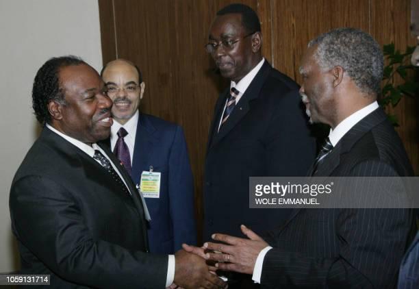 President Ali Ben Bongo Ondimba of Gabon shakes hands with former South African President Thabo Mbeki as Prime Minister of Ethiopia Meles Zenawi and...