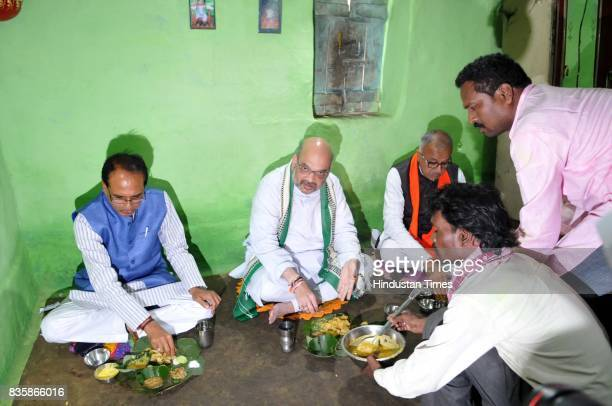 President Amit Shah along with Chief Minister Shivraj Singh Chouhan having lunch at the residence of tribal Kamal Singh Uike who belongs to Gond...