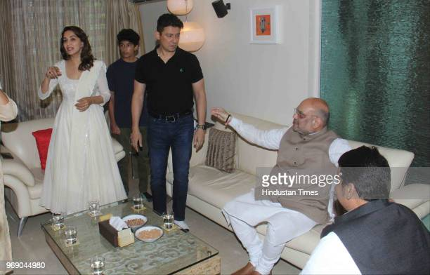 President Amit Shah along with Maharashtra CM Devendra Fadnavis meets Bollywood actor Madhuri Dixit with her husband Sriram Nene at her residence as...