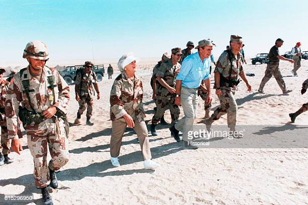 President and Barbara Bush accompanies General Norman Schawtzkopf and military personnel on a trek across the sand in Saudi Arabia November 22 1990