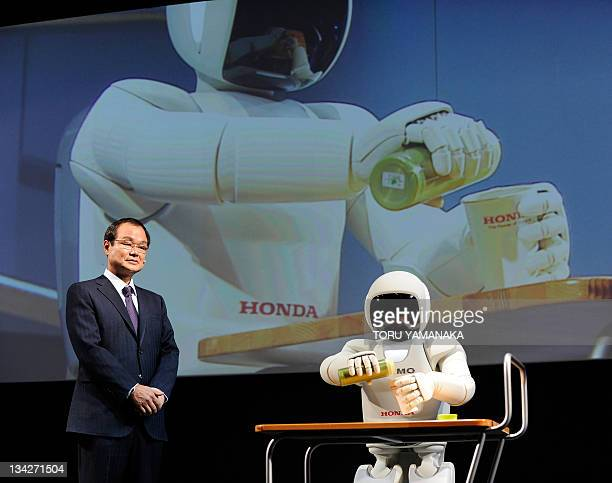 President and CEO of Japan's Honda Motor Takanobu Ito looks at its humanoid robot ASIMO pouring orange juice into a cup during the Tokyo Motor Show...