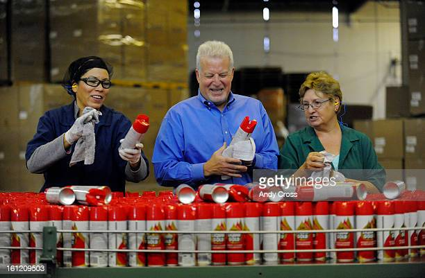 DENVER CO President and CEO of Scott's Liquid Gold Mark Goldstein center has a laugh and lends a hand to workers Alma Renteria left and Evelyn Hand...