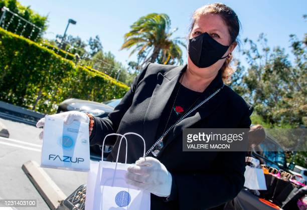 President and drive-through gifting event organizer Nathalie Dubois-Sissoko poses with some of the gifts at the Luxe hotel ahead of the Golden Globe...