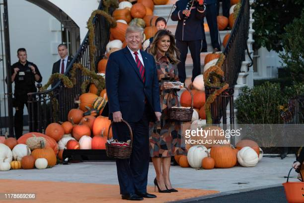 US President and First Lady Melania Trump arrive to hand out candy for children at a Halloween celebration at the White House in Washington DC on...