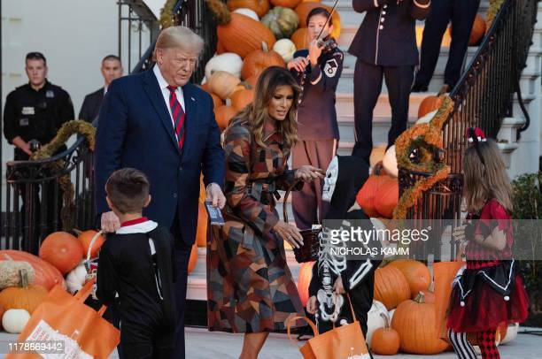US President and First Lady Melania Trump hand out candy for children at a Halloween celebration at the White House in Washington DC on October 28...