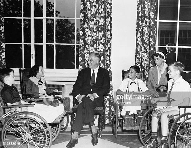 President and Mrs. Roosevelt enjoying after-luncheon conversation with little patients of the Warm Springs Foundation.