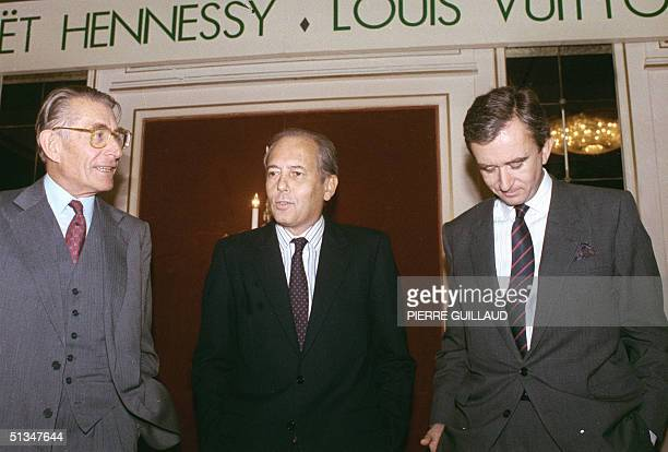 President and vice president of Louis VuittonMeot Henesy Alain Chevalier and Henry Racamier president of Financiere Agache Bernard Arnault chat...