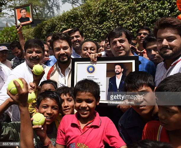 President Anurag Thakur distributing the cricket bat and ball to children as he was greeted by supporters at his residence on May 23 2016 in New...