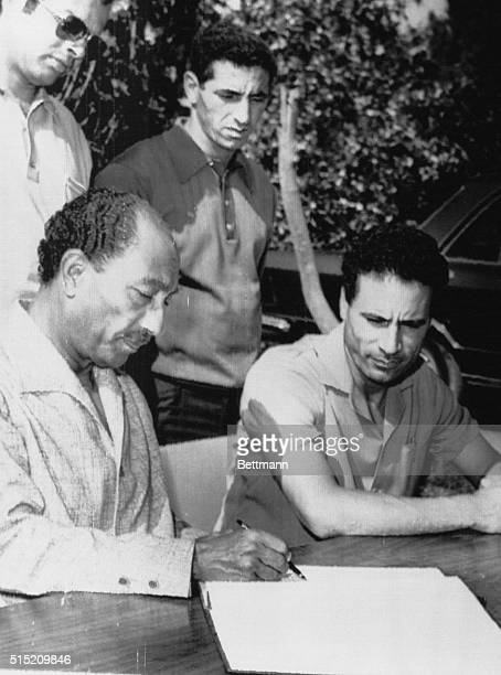 President Anwar Sadat and Libyan leader Colonel Muammar alQaddafi look over communiqué upon conclusion of three days of talks here 8/29 Sadat and...