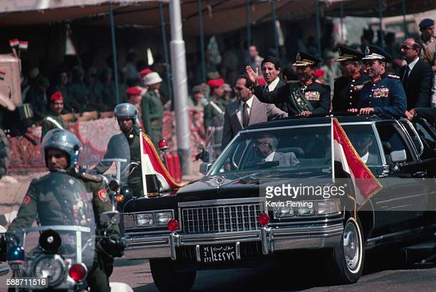 President Anwar Sadat rides in an open limosine along a road in Cairo on his way to a military parade honoring the October War of 1973 Sadat would be...