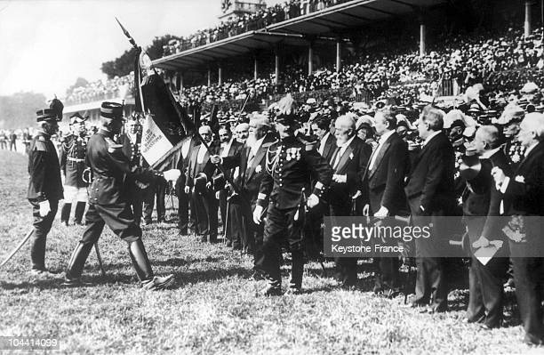 President Armand FALLIERES surrounded by members of the Government handing a flag to a regiment which had glorious campaigns during the inspection of...