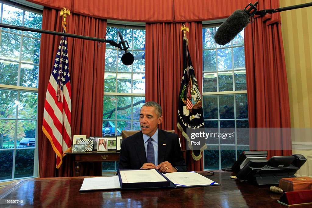U.S. President Barack Obam alooks at the bipartisan budget bill 2015 as he speaks to the media before he signs the bill into lawin the Oval Office of the White House November 2, 2015 in Washington, DC. Obama is traveling to New Jersey where he will talk about criminal justice reform and re-entry for formerly jailed people and he will later travel to New York for Democratic fund raisers.