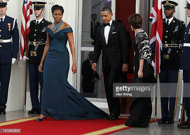 S President Barack Obama accidentially steps on First lady Michelle Obama's dress as they walk onto the North Portico before the arrival of British...