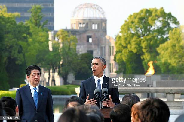 US President Barack Obama addresses the media while Japanese Prime Minister Shinzo Abe listens after offering wreaths at the cenotaph at the...