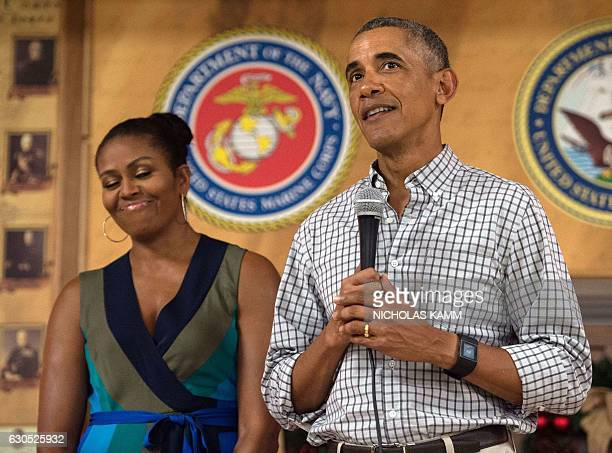President Barack Obama addresses troops with First Lady Michelle Obama at Marine Corps Base Hawaii in Kailua on December 25, 2016. / AFP / NICHOLAS...