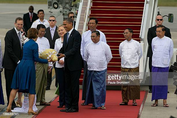 President Barack Obama alongside Secretary of State Hillary Clinton and Burmese Foreign minister Wunna Maung Lwin are greeted with flowers as they...