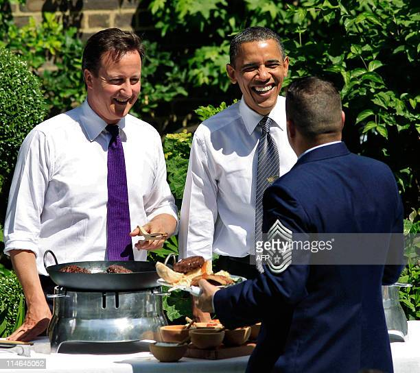 President Barack Obama and Britain's Prime Minister David Cameron serve BBQ to a soldier during an event hosted by Samantha Cameron and First Lady...