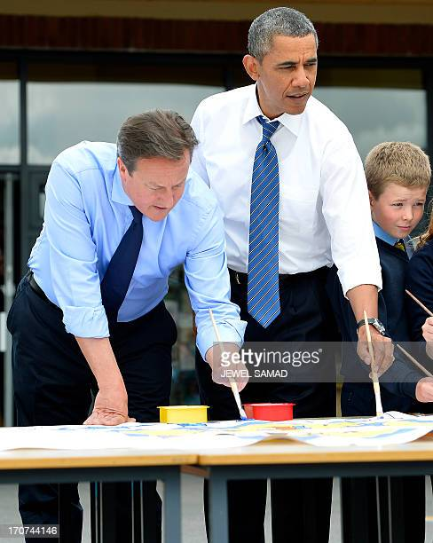 US President Barack Obama and British Prime Minister David Cameron help schoolchildren painting during a visit to a classroom at Enniskillen...