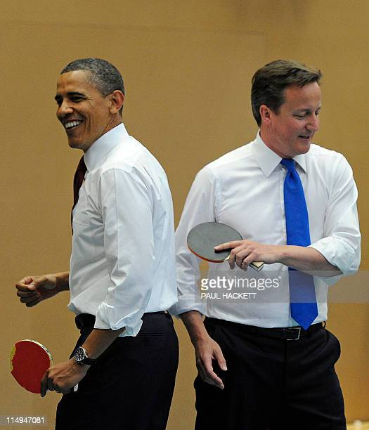President Barack Obama and British Prime Minister David Cameron joke as play table tennis with students of the Globe Academy school in London on May...
