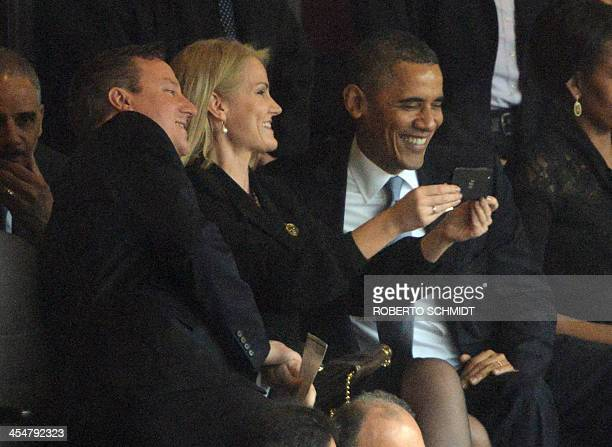 US President Barack Obama and British Prime Minister David Cameron pose for a selfie picture with Denmark's Prime Minister Helle Thorning Schmidt...