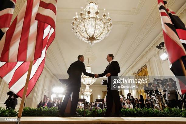 S President Barack Obama and British Prime Minister David Cameron shake hands after holding a joint news conference in the East Room at the White...