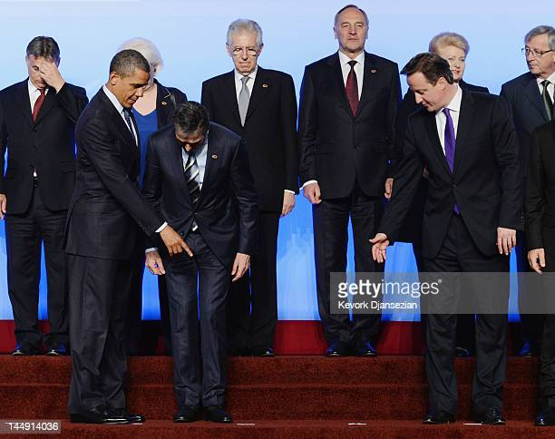 S President Barack Obama and British Prime Minister David Cameron show NATO Secretary General Anders Fogh Rasmussen his place on the riser during a...