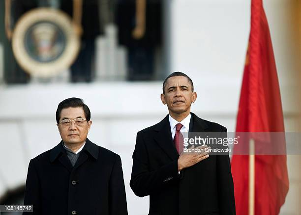 S President Barack Obama and Chinese President Hu Jintao stand together during a state arrival ceremony on the South Lawn of the White House January...