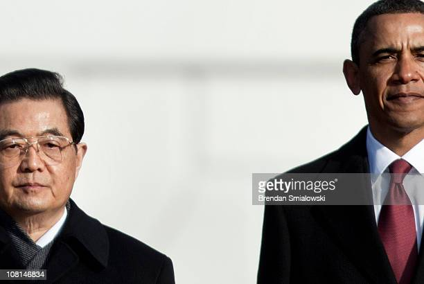President Barack Obama and Chinese President Hu Jintao stand together at the conclusion of a state arrival ceremony on the South Lawn of the White...