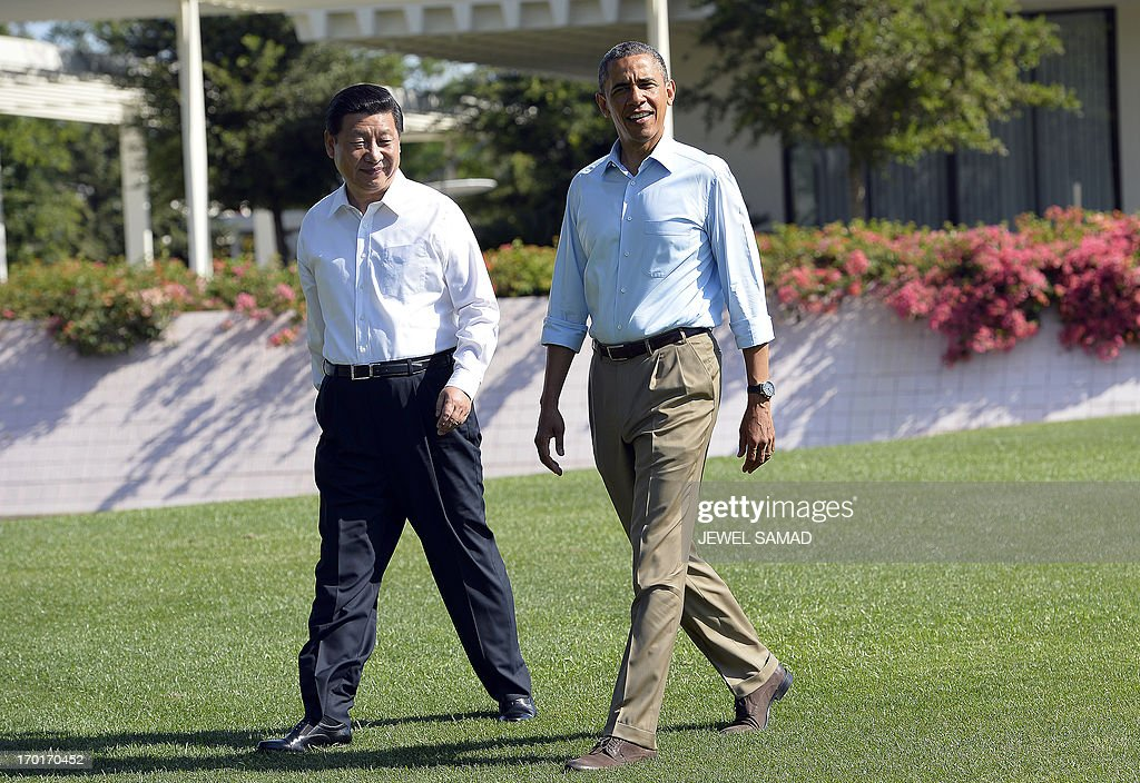 US President Barack Obama (R) and Chinese President Xi Jinping chat as they take a walk at the Annenberg Retreat at Sunnylands in Rancho Mirage, California, on June 8, 2013. Obama and Xi wrap up their debut summit Saturday, grasping for a personal understanding that could ease often prickly US-China relations. Skipping the usual summit pageantry, Obama and Xi went without neckties, in a departure from the stifling formality that marked Obama's halting interactions with China's ex-president Hu Jintao. AFP PHOTO/Jewel Samad