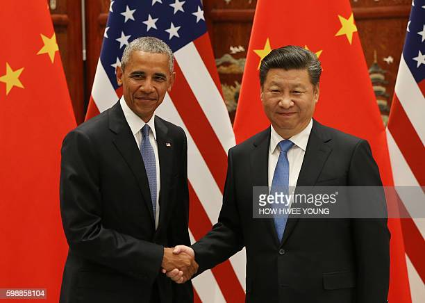 US President Barack Obama and Chinese President Xi Jinping shake hands during their meeting at the West Lake State Guest House in Hangzhou on...