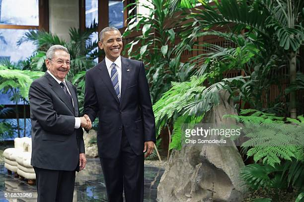 S President Barack Obama and Cuban President Raul Castro pose for photographs after greeting one another at the Palace of the Revolution March 21...