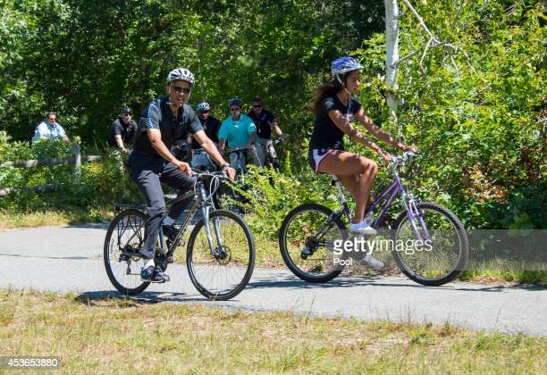 S President Barack Obama and daughter Malia Obama ride bikes along the Correllus State Bike Path on August 15 2014 outside of West Tisbury Martha's...