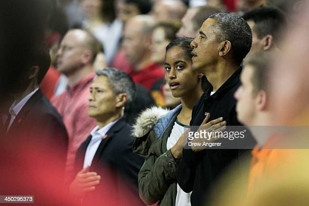 President Barack Obama and daughter Malia Obama stand during the National Athem before a men's NCCA basketball game between University of Maryland...