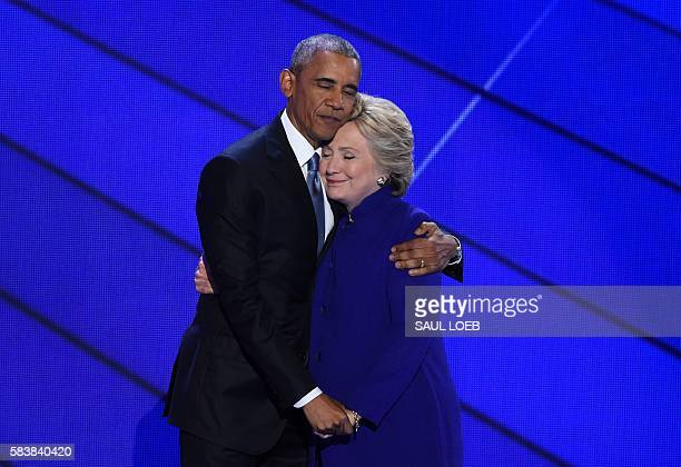 President Barack Obama and Democratic presidential nominee Hillary Clinton embrace on stage during Day 3 of the Democratic National Convention at the...