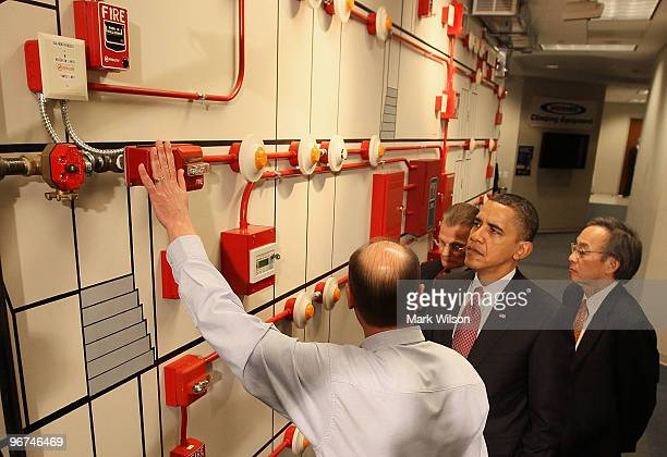 US President Barack Obama and Energy Secretary Steven Chu get a tour of a fire alarm panel from teacher Rhett Roe during a visit to the jobs training...