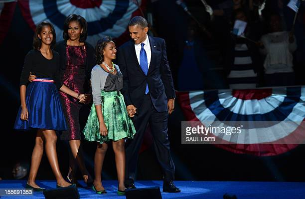 US President Barack Obama and family arrive on stage after winning the 2012 US presidential election November 7 2012 in Chicago Illinois Obama swept...
