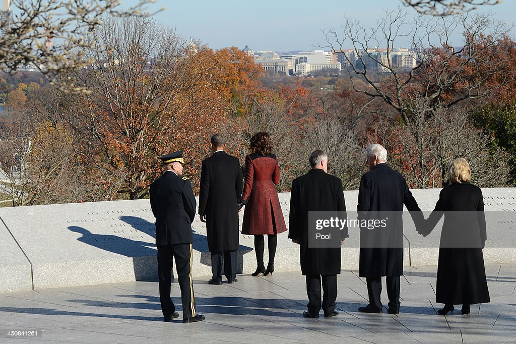 U.S. President Barack Obama (2nd L) and first lady Michelle Obama (3rd L) and former U.S. President Bill Clinton (2nd R) and former U.S. Secretary of State Hillary Clinton (R) looks at quotes inscribed at the at the grave site for President John F. Kennedy, after a wreath laying ceremony at Arlington National Cemetery November 20, 2013 in Arlington, Virginia. The 50th anniversary of the assassination of John F. Kennedy will be marked on November 22.