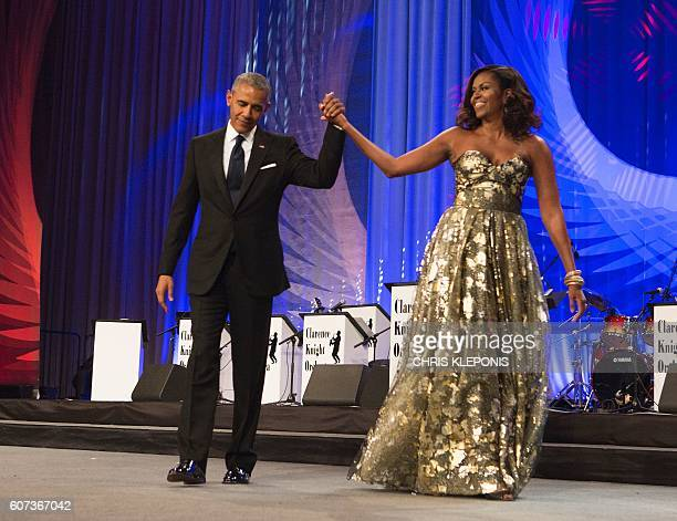 President Barack Obama and First Lady Michelle Obama arrive on stage during the Congressional Black Caucus Foundation's Phoenix Awards Dinner on...