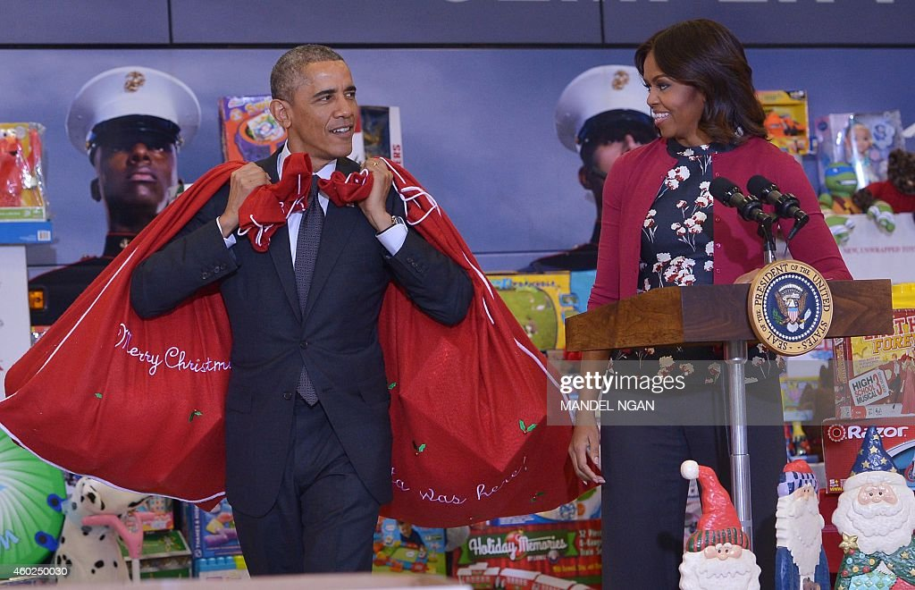 US President Barack Obama and First Lady Michelle Obama arrive to deliver toys and gifts for the Marine Corps Toys for Tots campaign on December 10, 2014 at Bolling Air Force Base in Washington, DC. The gifts were donated by staff of the presidential office.