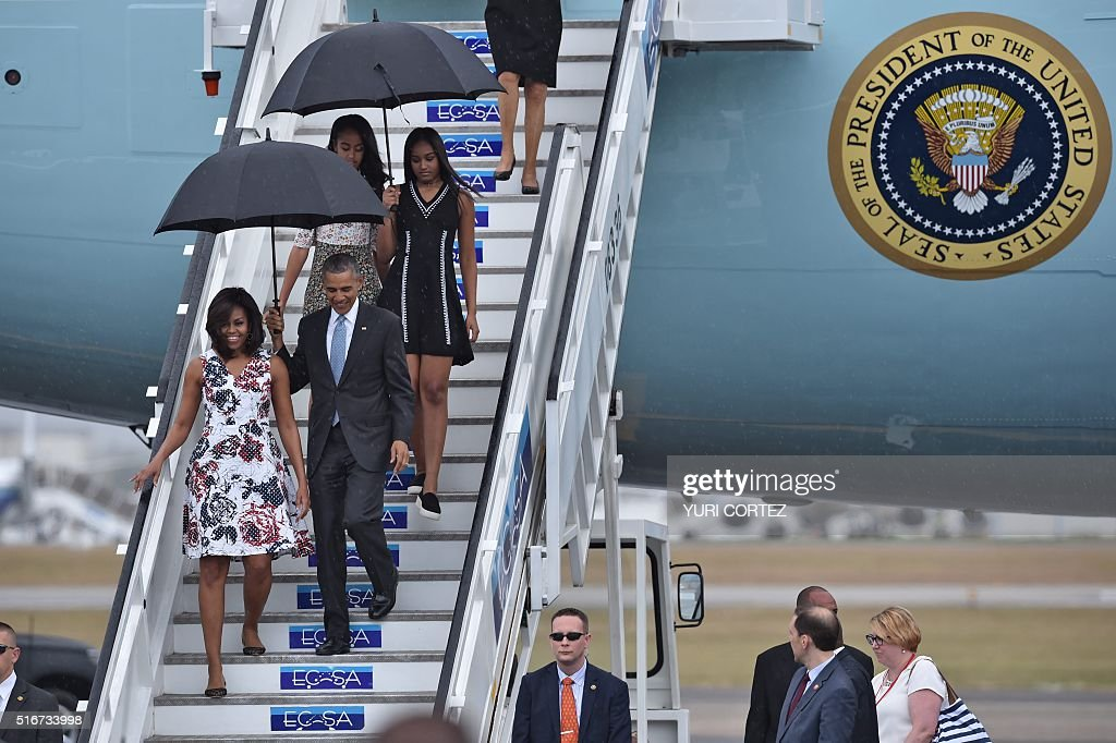 US President Barack Obama and First Lady Michelle Obama arrive with their daughters Sasha and Malia (behind) at Jose Marti international airport in Havana on March 20, 2016. Obama, who is on a historic three-day visit to the communist-ruled island, flew to Cuba Sunday to bury the hatchet in a more than half-century-long Cold War standoff, but the arrest of dozens of dissidents just as his plane took off underlined the delicacy of the mission. AFP PHOTO/ Yuri CORTEZ / AFP / YURI