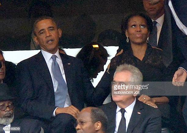 US President Barack Obama and First Lady Michelle Obama attend the memorial service for late South African President Nelson Mandela at Soccer City...