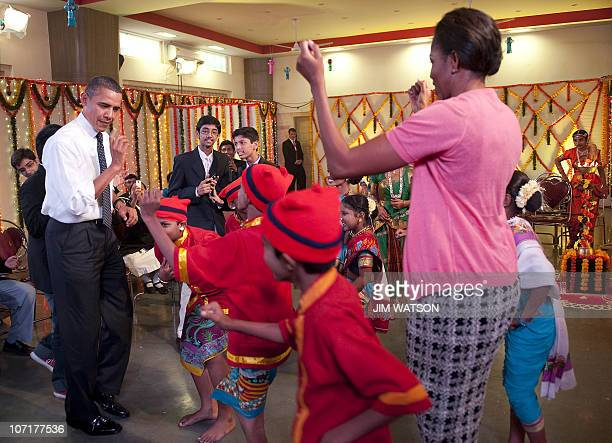 US President Barack Obama and First Lady Michelle Obama dance during a cultural event at The Holy Name High School in Mumbai on November 7 2010...