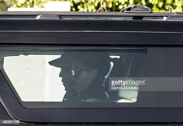 US President Barack Obama and First Lady Michelle Obama drive out from their residence in Kailua on December 27 2014 as they make their way tpo the...