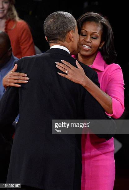 S President Barack Obama and first lady Michelle Obama embrace after a town hall style debate at Hofstra University October 16 2012 in Hempstead New...