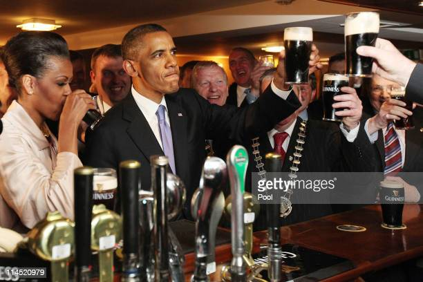 President Barack Obama and First Lady Michelle Obama enjoy a glass of Guinness in his ancestral home of Moneygall on May 23 2001 in Moneygall Ireland...