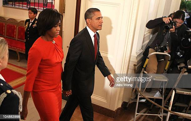 S President Barack Obama and first lady Michelle Obama enter the East Room for a presentation ceremony of a Medal of Honor October 6 2010 at the...