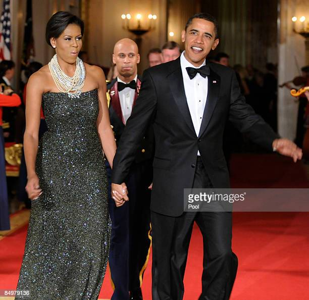 S President Barack Obama and first Lady Michelle Obama enter the East Room for entertainment after a blacktie dinner at the White House on February...